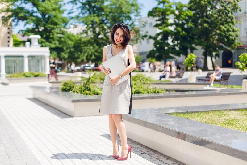 Het vrij donkerbruine meisje in grijze kleding en wijnhielen bevindt zich in park in de stad Zij houdt laptop en kijkt schuw stock afbeeldingen