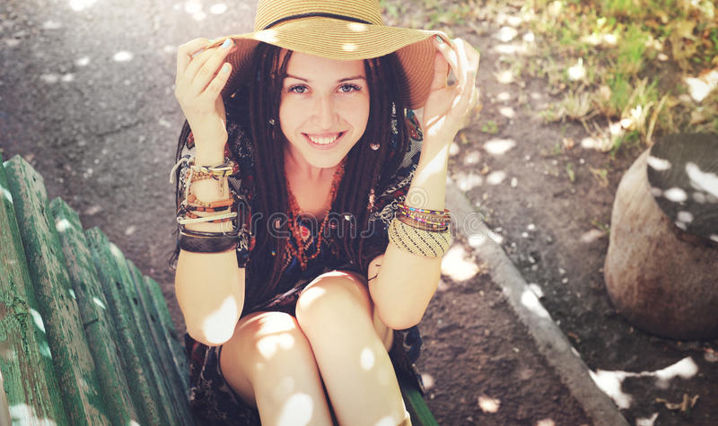 Het vrij glimlachende jonge meisje met dreadlocks kleedde zich in bohostijl, openlucht rusten stock afbeelding