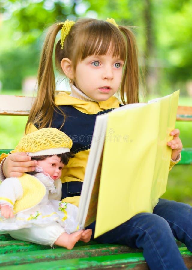 Het vrij jonge meisje leest een boek met haar pop stock afbeelding