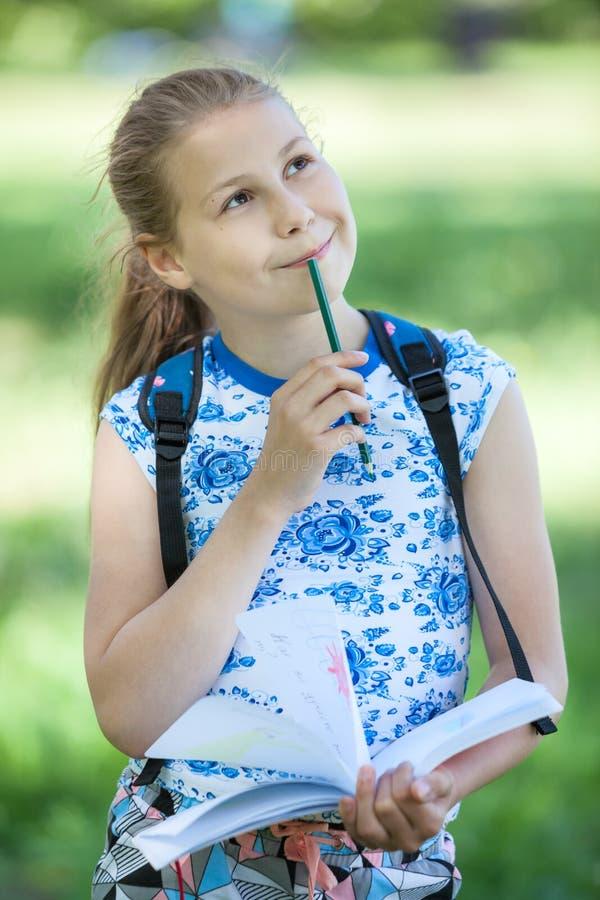Het vrij jonge meisje maakt schetsen van landschappen in aard met kleurenpotlood stock foto