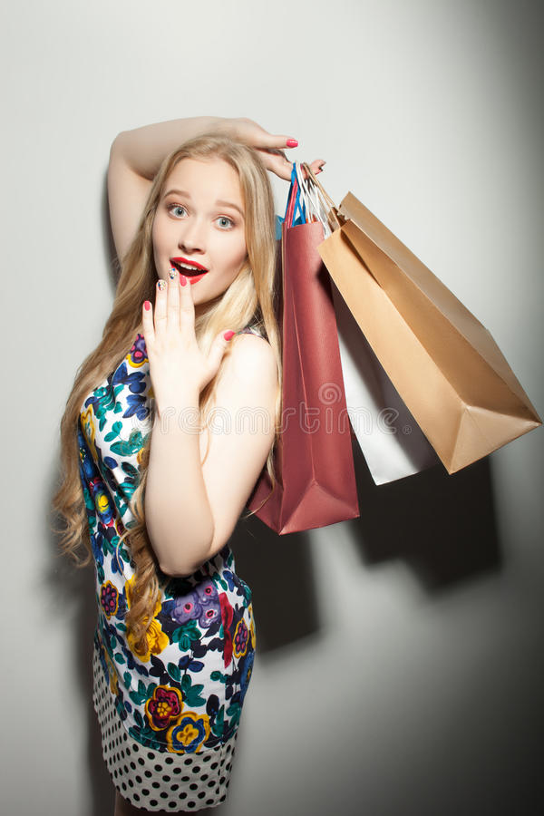 Het vrij jonge meisje met pakketten drukt schok uit stock afbeeldingen