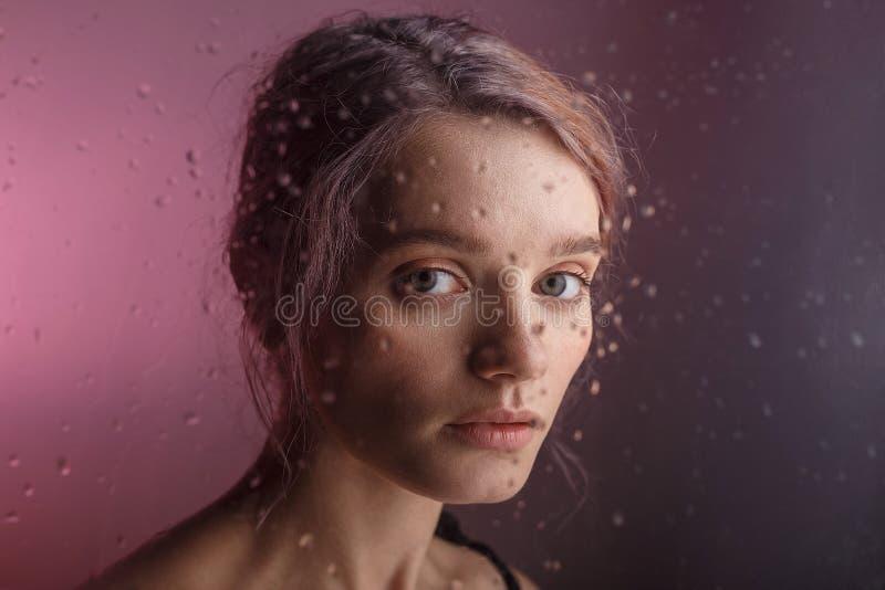 Het vrij jonge meisje onderzoekt camera op purpere achtergrond de onscherpe dalingen van water reduceren het glas voor haar gezic royalty-vrije stock afbeeldingen