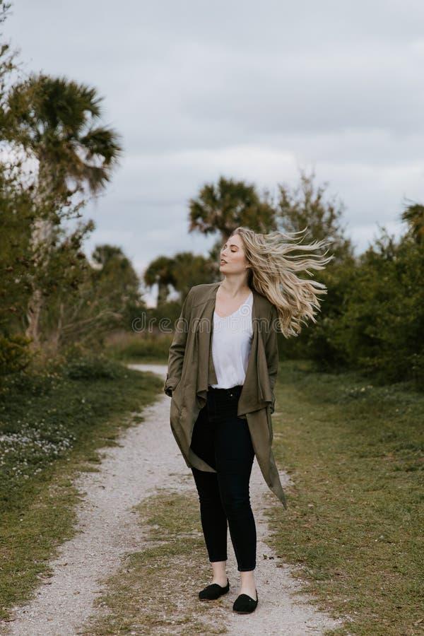 Het vrij Jonge Model van de Schoonheidsvrouw met Schitterend Lang Blond Haar die in de Wind blazen die voor Portretschoten buiten stock foto's