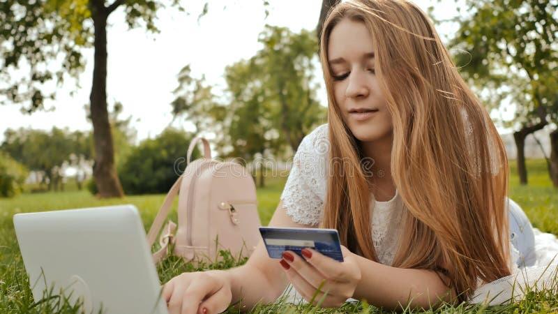 Het vrij jonge studentenmeisje maakt aankopen online gebruikend een creditcard en laptop computer royalty-vrije stock foto's