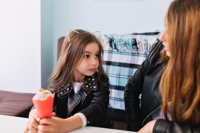 Het vrij langharige meisje in zwart jasje wil geen roomijs met haar mamma delen Portret van jonge modieuze vrouw en stock foto