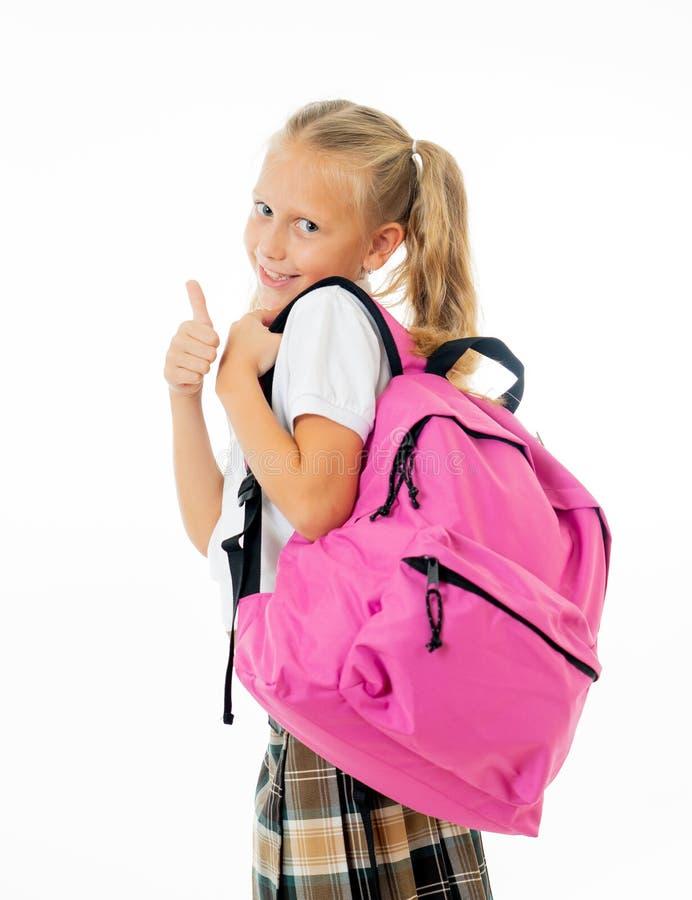 Het vrij leuke meisje van het blondehaar met een roze schooltas die camera bekijken die duim op gebaar gelukkig om naar geïsoleer royalty-vrije stock foto