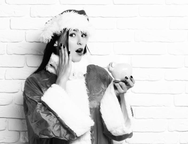 Het vrij leuke sexy santameisje of de verraste donkerbruine vrouw in nieuwe jaarsweater en Kerstmis of Kerstmishoed houden roze p royalty-vrije stock foto's