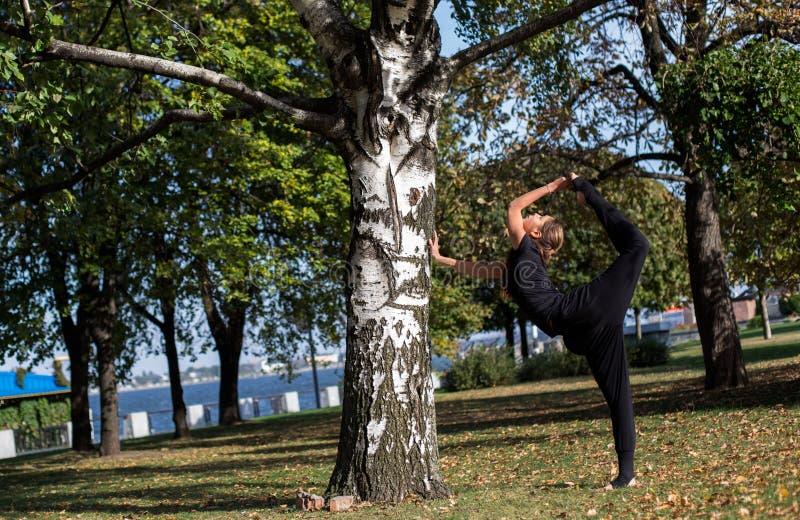 Het vrij slanke meisje doet yoga in het park Status bij de voet saldi in de spleten royalty-vrije stock foto