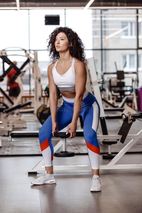 Het vrij slanke meisje met donker krullend haar gekleed in een sportkleding doet terug hurkzit met zware domoor in de moderne gym stock afbeelding