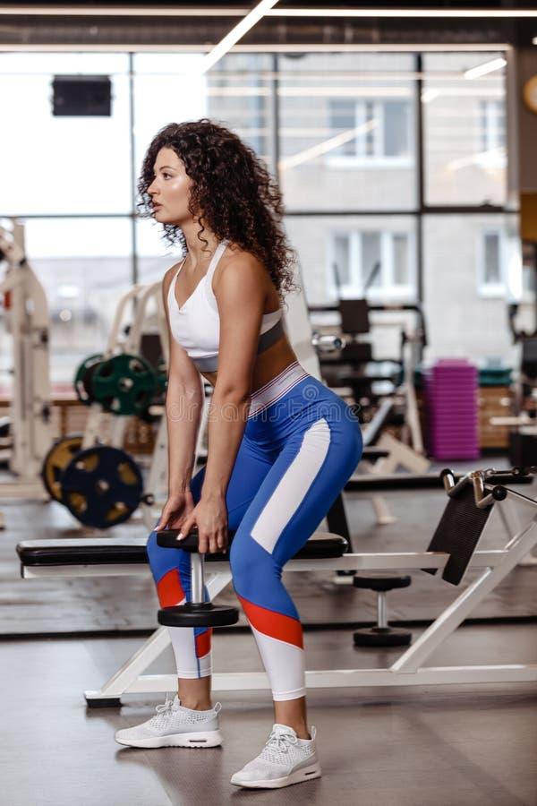 Het vrij slanke meisje met donker krullend haar gekleed in een sportkleding doet terug hurkzit met zware domoor in de moderne gym stock foto's
