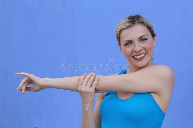 Het vrije stijl mooie blonde vrouw uitrekken zich op blauwe achtergrond met exemplaarruimte royalty-vrije stock fotografie
