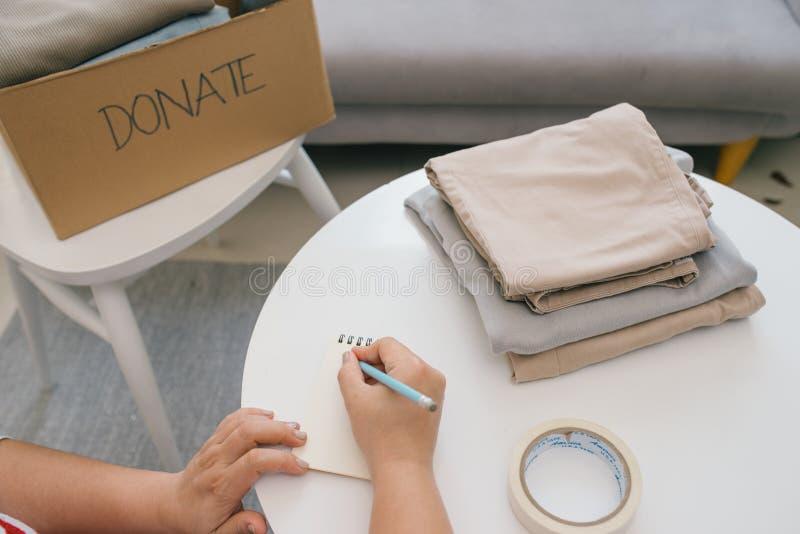 Het vrijwilligers schrijven in notitieboekje en dichtbijgelegen kartondoos met kleren stock fotografie