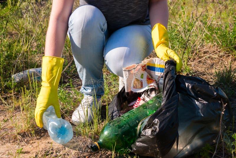 Het vrijwilligersmeisje in gele handschoenen verzamelt huisvuil royalty-vrije stock fotografie