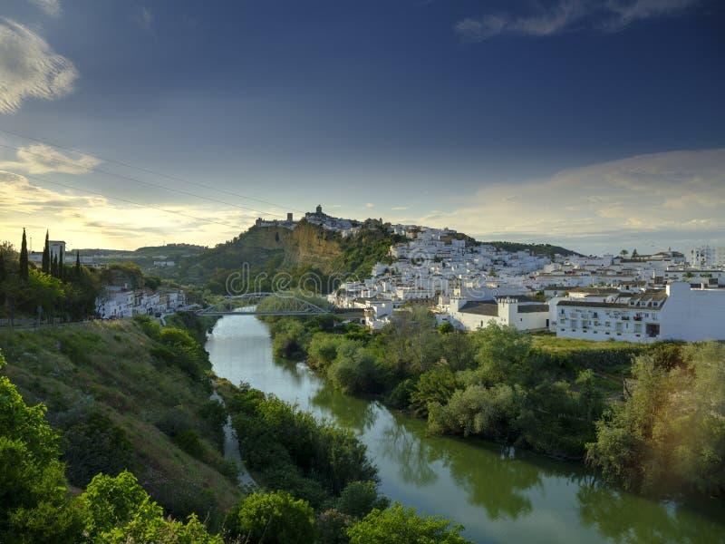 Het vroege avondzonsondergang lichte vallen op de stad van Arcos de la Frontera, Andalucia, Spanje stock afbeelding