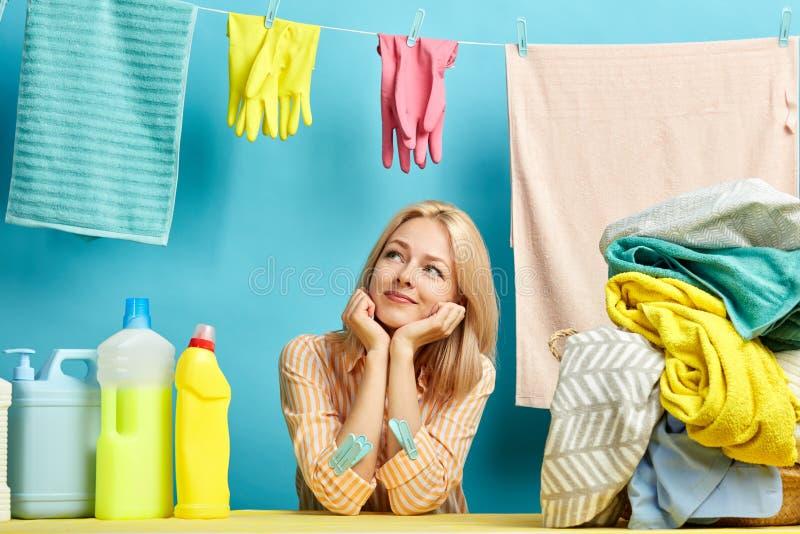 Het vrolijke aantrekkelijke meisje heeft haar wasserij gebeëindigd Zij droomt over iets stock fotografie