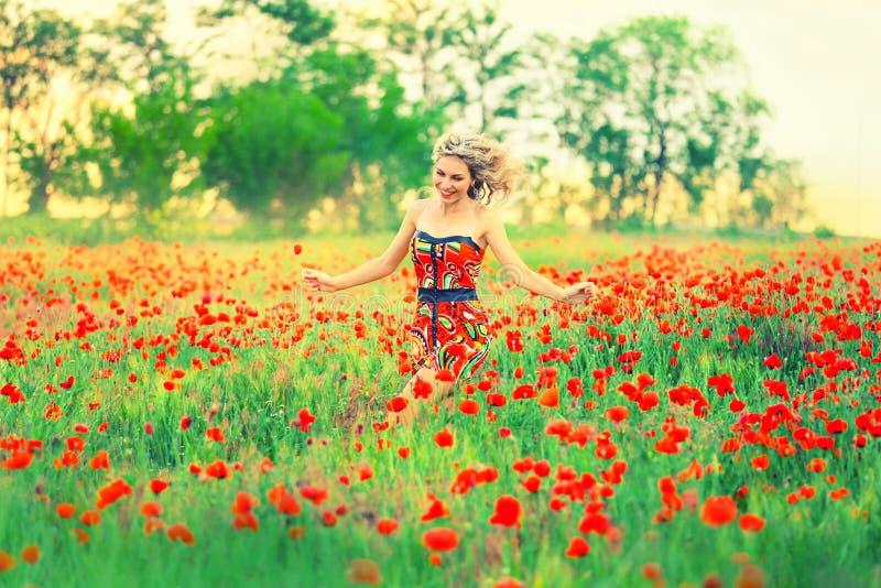 Het vrolijke aantrekkelijke mooie meisje met blonde krullende het vliegen haarlooppas over het de papavergebied en lach, de wind  stock foto's