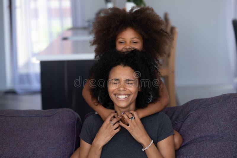 Het vrolijke Afrikaanse mamma en jong geitjedochter het lachen thuis omhelzen royalty-vrije stock afbeeldingen