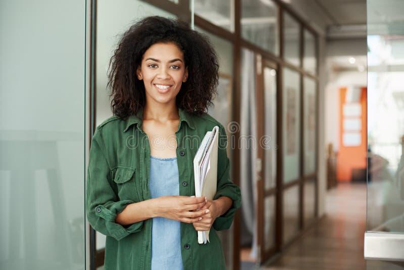 Het vrolijke Afrikaanse mooie studente glimlachen die de boeken van de cameraholding op universiteit bekijken Het concept van het stock fotografie