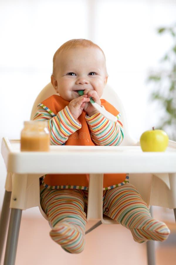 Het vrolijke babykind eet voedsel zelf met lepel Portret van gelukkige jong geitjejongen in hoog-stoel stock foto
