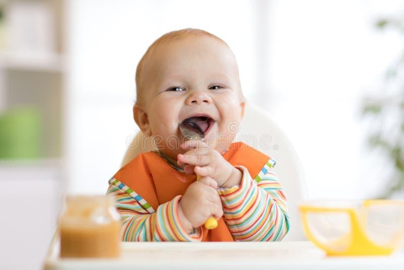 Het vrolijke babykind eet voedsel zelf met lepel Portret van gelukkige jong geitjejongen in hoog-stoel royalty-vrije stock fotografie