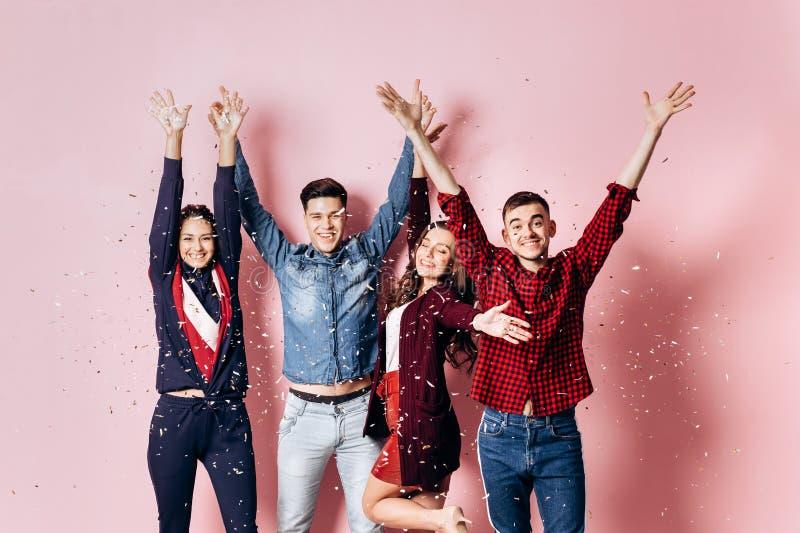 Het vrolijke bedrijf van twee meisjes en twee kerels gekleed in modieuze kleren bevinden zich en hebben pret met confettien op a royalty-vrije stock fotografie