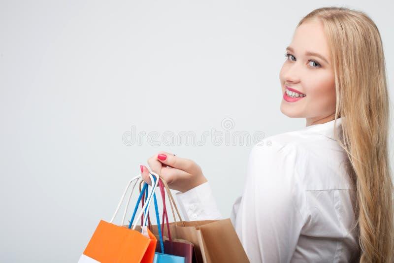 Het vrolijke blonde jonge meisje doet het winkelen stock afbeeldingen