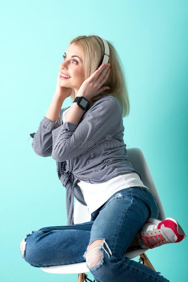 Het vrolijke blonde meisje luistert aan lied stock afbeeldingen
