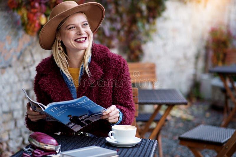 Het vrolijke blonde meisje onderhouden met tijdschrift openlucht stock afbeelding
