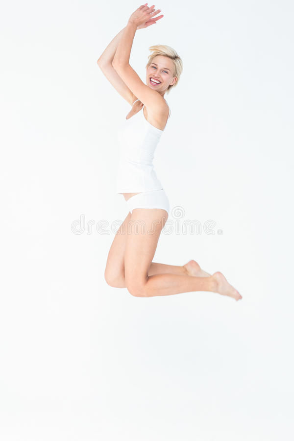 Het vrolijke blondevrouw springen stock afbeelding
