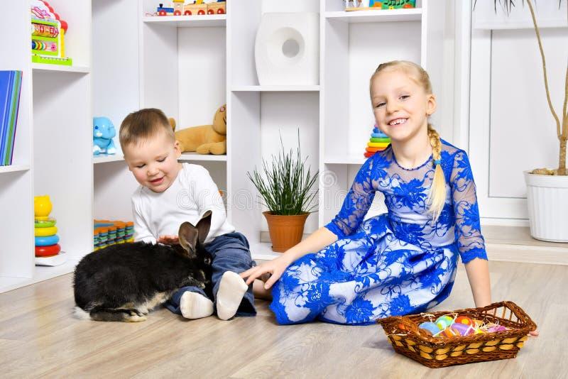 Het vrolijke broer en zuster spelen met een konijn royalty-vrije stock foto