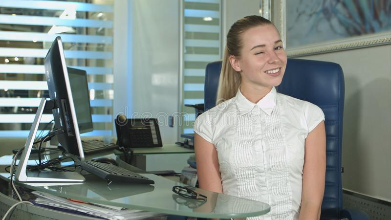 Het vrolijke bureau-arbeider beduimelt tonen omhoog het bekijken camera stock afbeelding