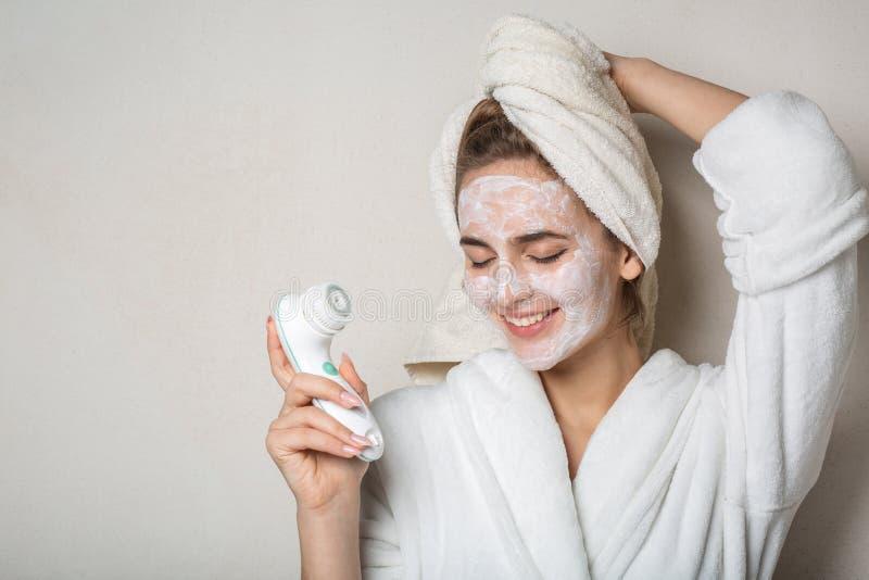 Het vrolijke donkerbruine model stellen met bevochtigende roommasker en gezichtsreinigingsmachine Lege ruimte royalty-vrije stock afbeeldingen