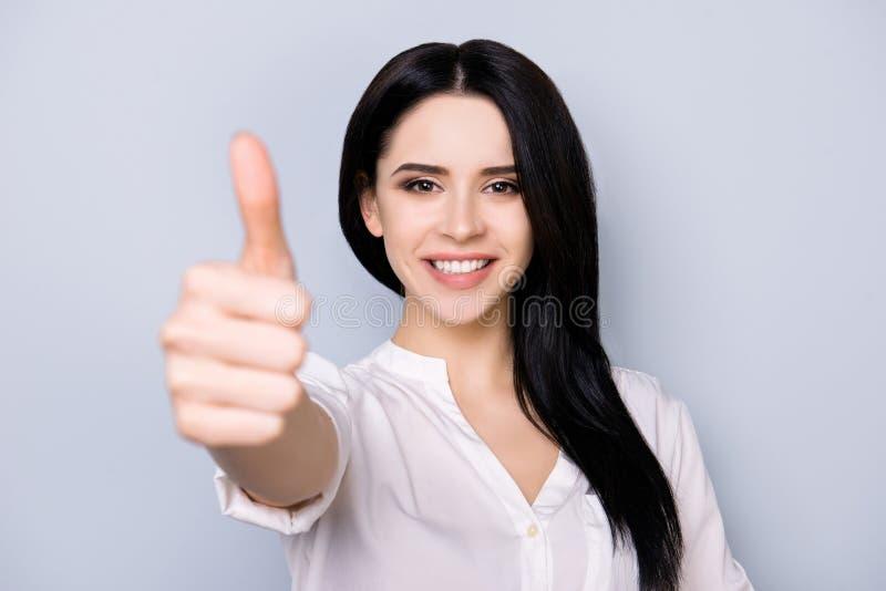 Het vrolijke donkerbruine mooie meisje met het richten van glimlach gesturing a stock afbeeldingen