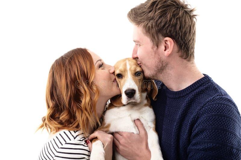 Het vrolijke echtpaar kust hun hond stock afbeelding