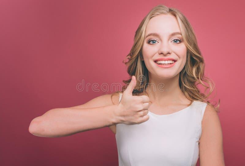 Het vrolijke en aantrekkelijke jongere houdt haar duim tegen en glimlacht Zij is zeer vrolijk Geïsoleerdo op roze royalty-vrije stock fotografie