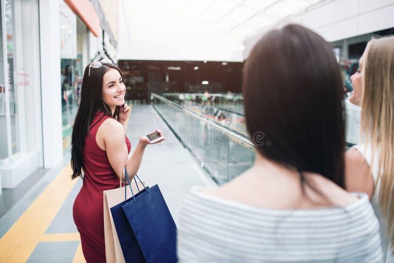Het vrolijke en mooie meisje in rode kleding kijkt terug naar haar vrienden en het glimlachen Ook houdt zij twee zakken en telefo royalty-vrije stock afbeelding