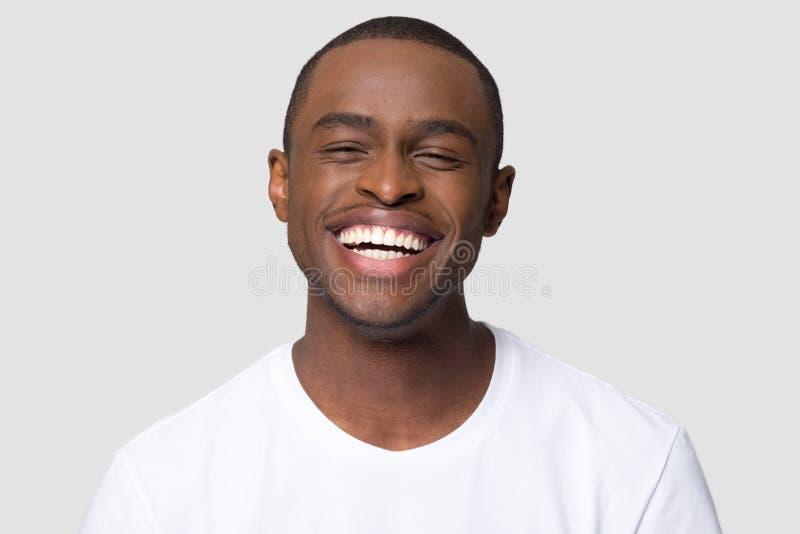 Het vrolijke gelukkige Afrikaanse millennial mens lachen geïsoleerd op studioachtergrond royalty-vrije stock afbeeldingen