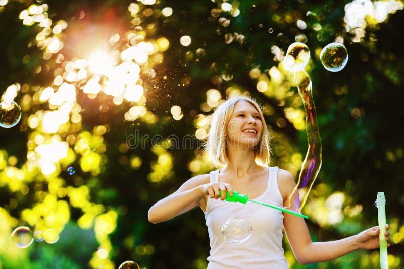 Het vrolijke gelukkige meisje met mooie glimlach blaast bellen stock foto's