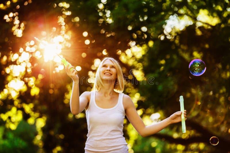 Het vrolijke gelukkige meisje met mooie glimlach blaast bellen royalty-vrije stock fotografie