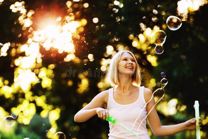 Het vrolijke gelukkige meisje met mooie glimlach blaast bellen royalty-vrije stock foto's