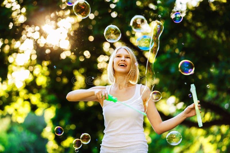Het vrolijke gelukkige meisje met mooie glimlach blaast bellen royalty-vrije stock foto