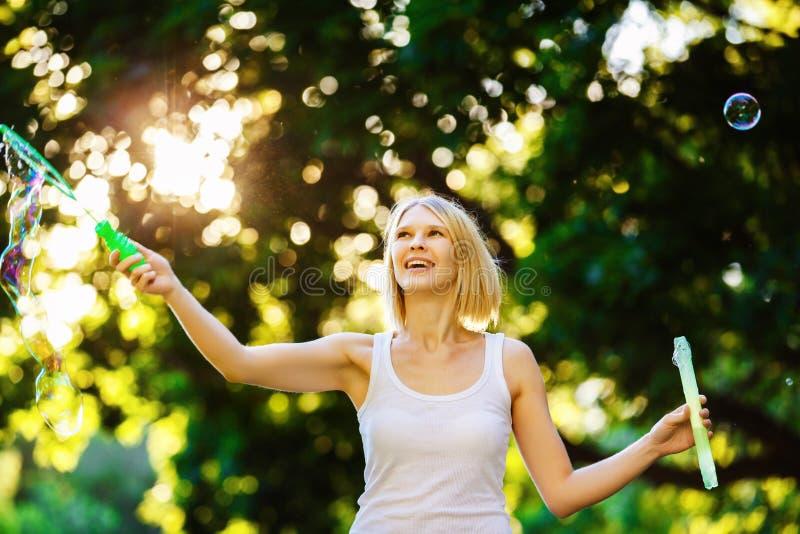 Het vrolijke gelukkige meisje met mooie glimlach blaast bellen bij s stock afbeelding