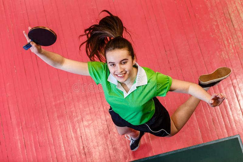 Het vrolijke het glimlachen tienermeisje springen Tienermeisje die een pingpongracket houden royalty-vrije stock fotografie