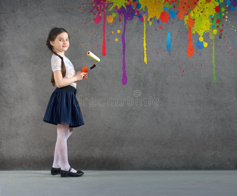 Het vrolijke glimlachende jonge meisje het kind op de achtergrondmuur trekt kleurde verven makend creatieve reparaties stock afbeelding