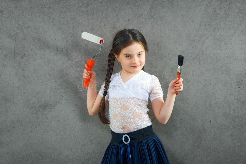 Het vrolijke glimlachende jonge meisje het kind trekt op de achtergrondmuurkleuren die creatieve reparaties maken stock afbeeldingen