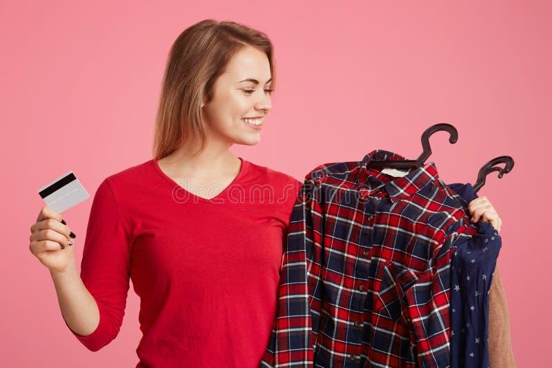 Het vrolijke glimlachende wijfje maakt succesvolle aankopen, bekijkt haar nieuwe kleren, houdt plastic kaart als het gaan voor ui royalty-vrije stock afbeelding
