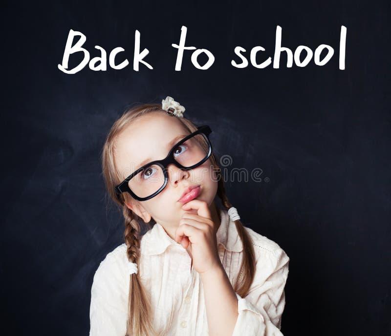 Het vrolijke grappige meisje denken Terug naar school en onderwijs stock foto