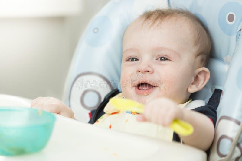 Het vrolijke het glimlachen babyjongen spelen met lepel in highchair royalty-vrije stock afbeelding