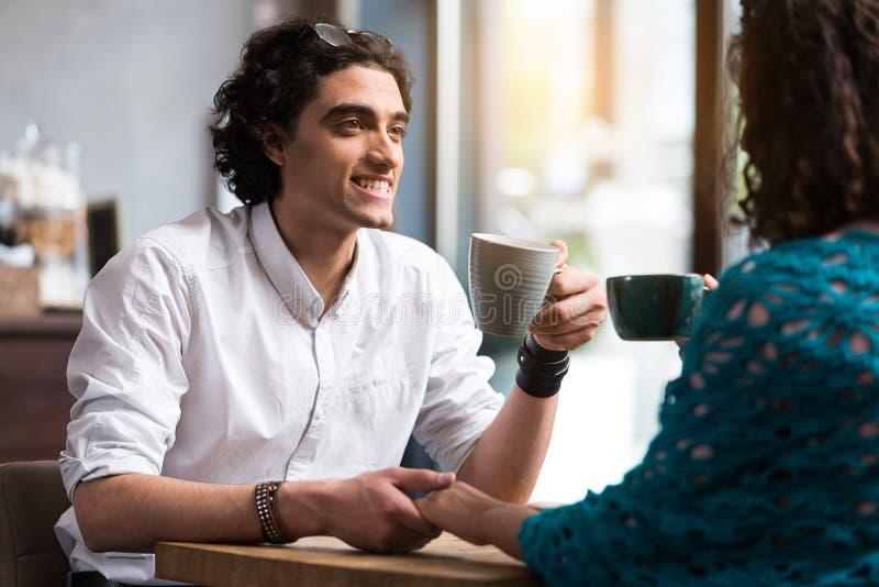 Het vrolijke het houden van paar ontspannen in koffie stock afbeelding