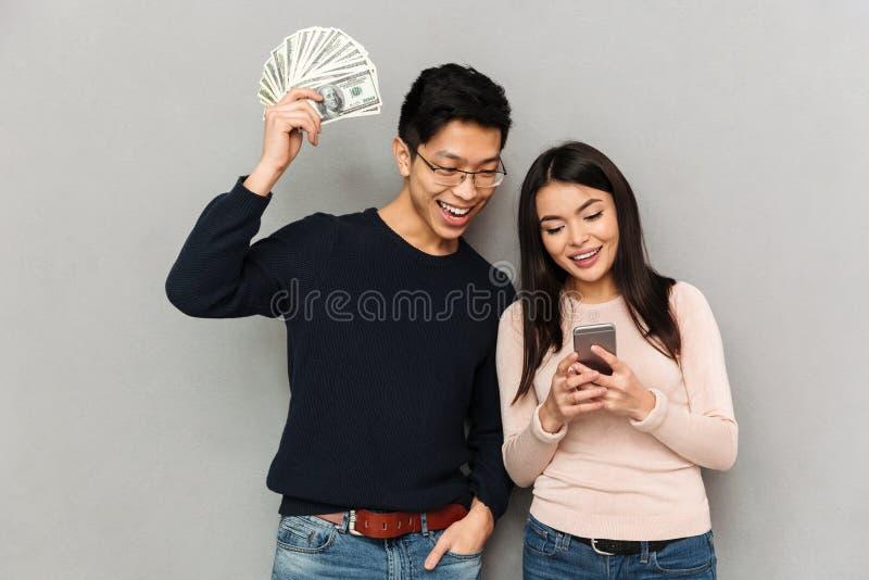 Het vrolijke jonge Aziatische het houden van geld van de paarholding en mobiele telefoon stock afbeelding